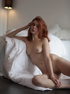 Riccarda alluring redhead riccarda displays her creamy body with pink nipples on the bed.