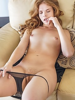 Dgil dgil seductively strips on the couch showing off her delectable pussy.
