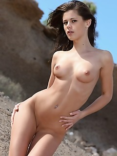 Caprice a caprice a erotically poses on the sandy field baring her delectable body.
