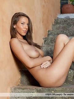 Mila i looks intensely towards the camera with a sultry, piercing gaze as she spreads her legs wide open