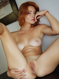Kika redhead bombshell with striking blue eyes, kika looks towards the camera with a striking stare as she poses nude, her magnificent large breasts a