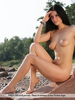 Mirelle a poses nude while wearing a red bead necklace