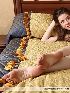 Kitana a poses sensually all over the bed displaying her petite, nubile body with long lean legs.