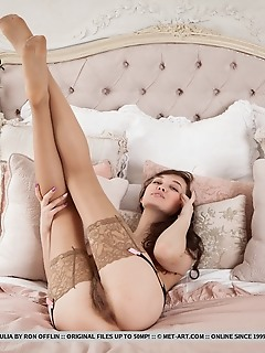 Ulia ulia sensually poses on the bed as she displays her unshaven pussy.