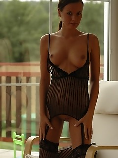 Nina's curvy body makes a stunning silhouette against the glass window.