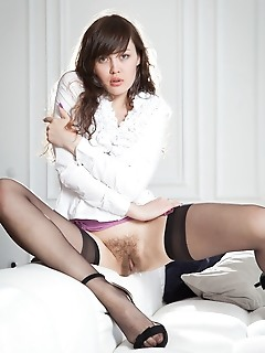Ulia ulia strips on the bed as she displays her hairy pussy.